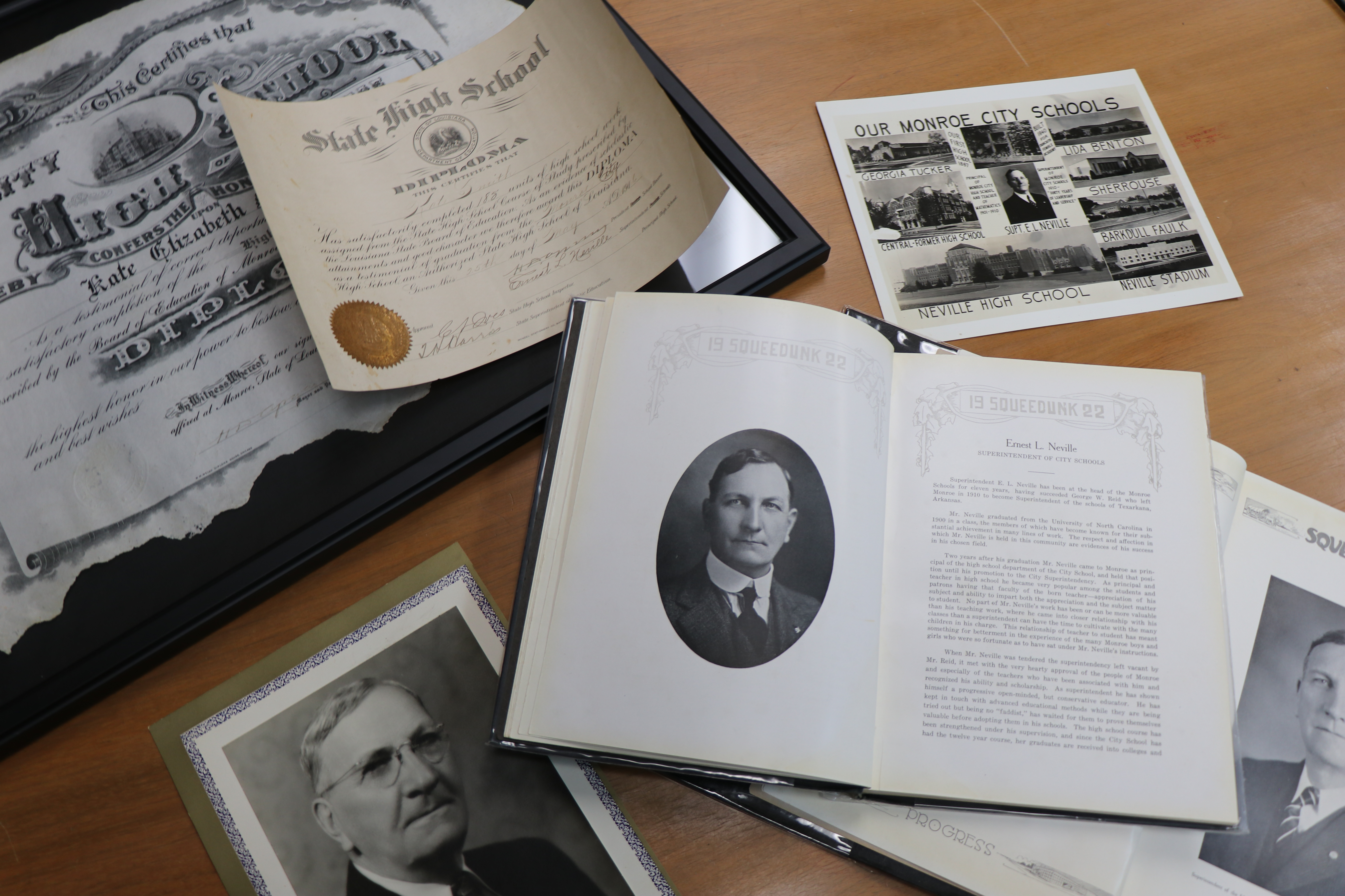A table featuring various historical items: a portrait of Ernest Long Neville, a high school diploma, the Squeedunk 1922 yearbook open to a portrait of Ernest Neville