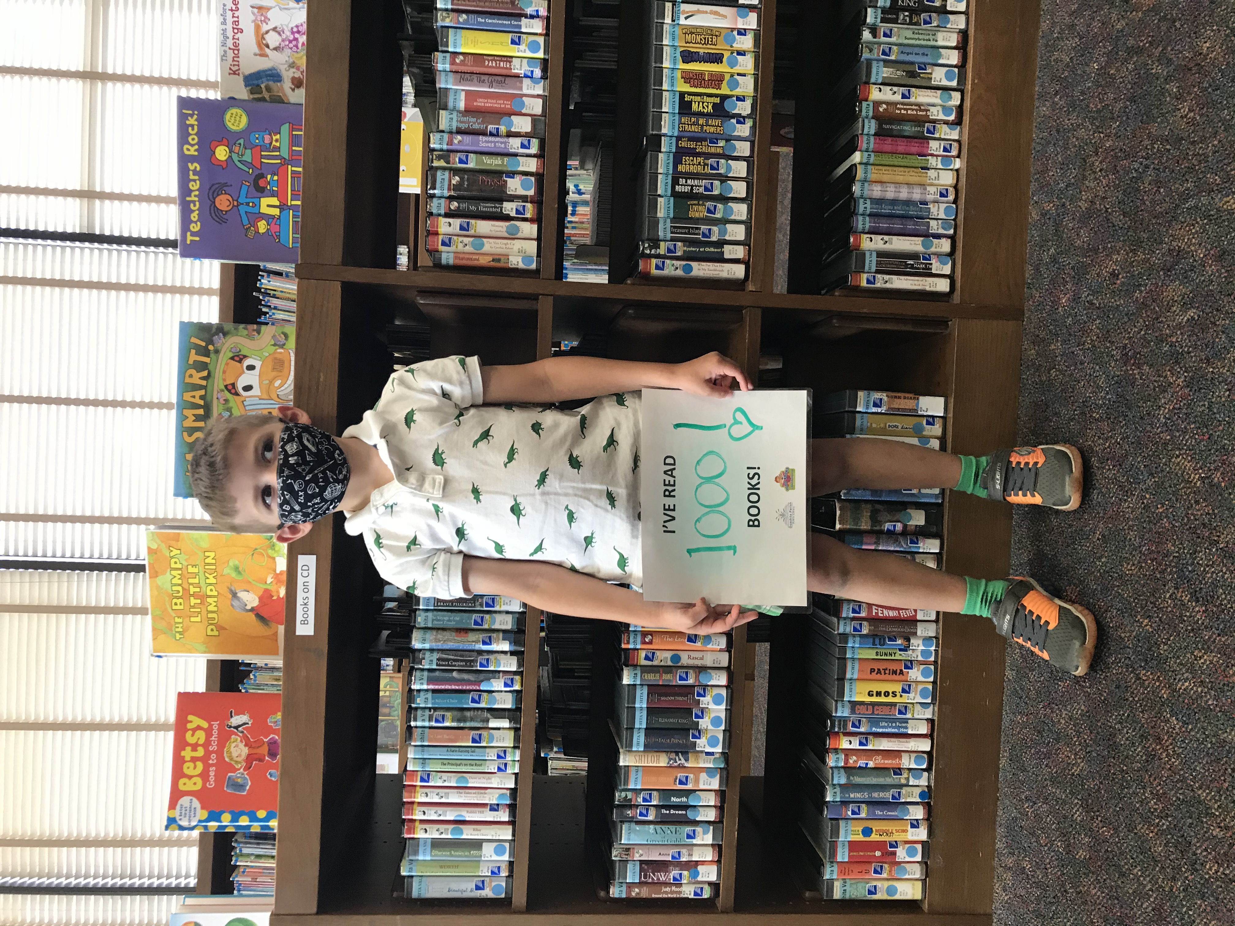 """A boy stands in front of a book shelf and holds a sign that says, """"I've read 1000 books!"""""""