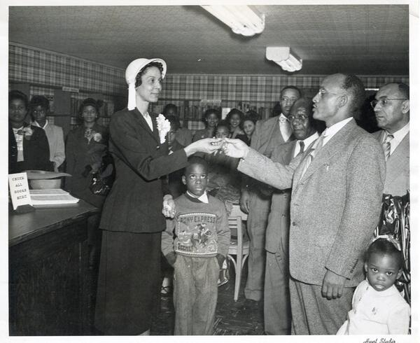 Mrs. Odalie S. Richardson (McDonald), receiving the key to the Carver Branch Library located at 109 ½ Powell's Alley, Monroe, from B.D. Robinson, representative of the Colored Chamber of Commerce, as his children Carl Dayton and LaSandra watch.