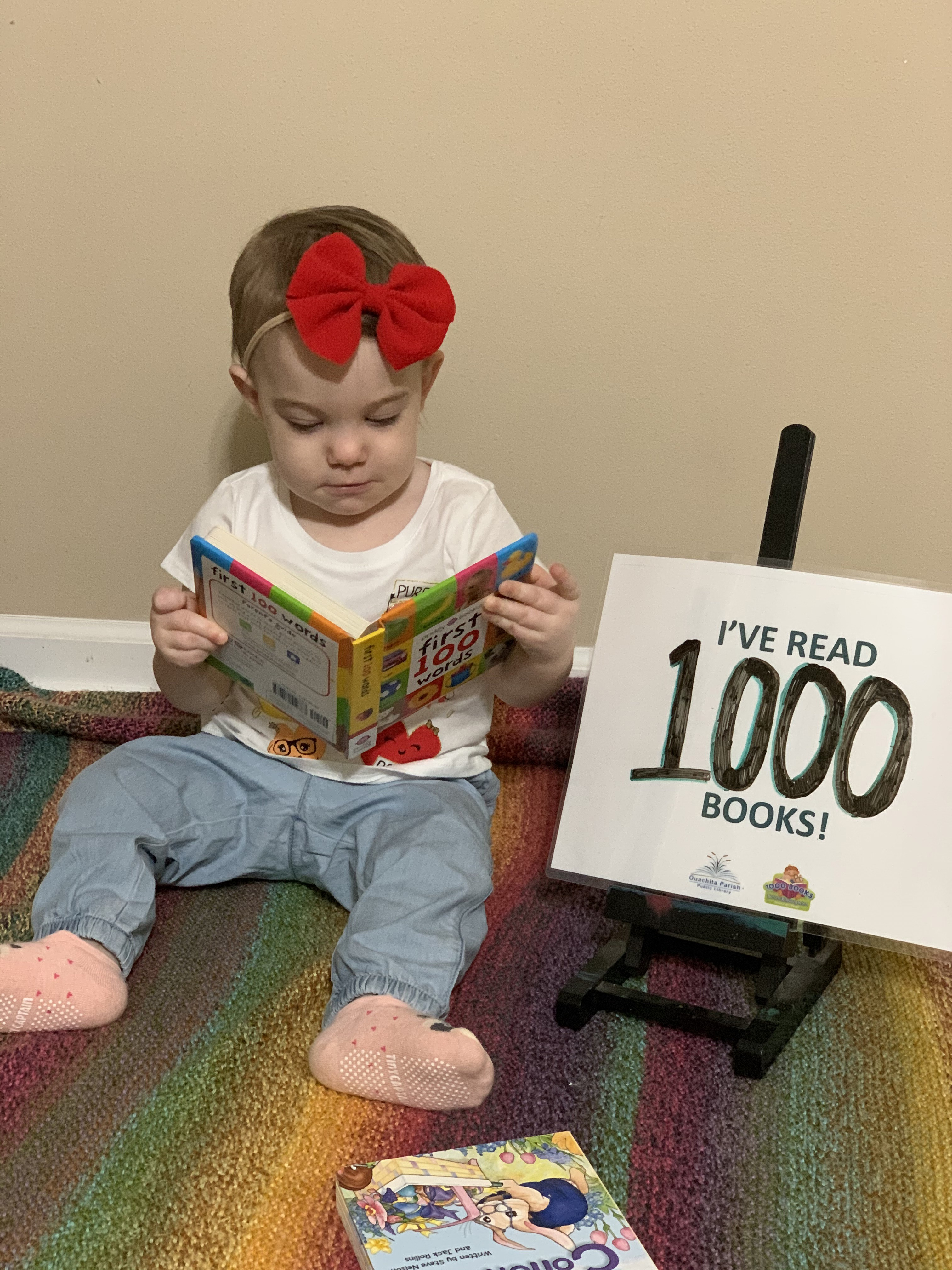 """A baby sits up with a book open in her lap. There is a sign next to her that says, """"I've read 1000 books!"""""""
