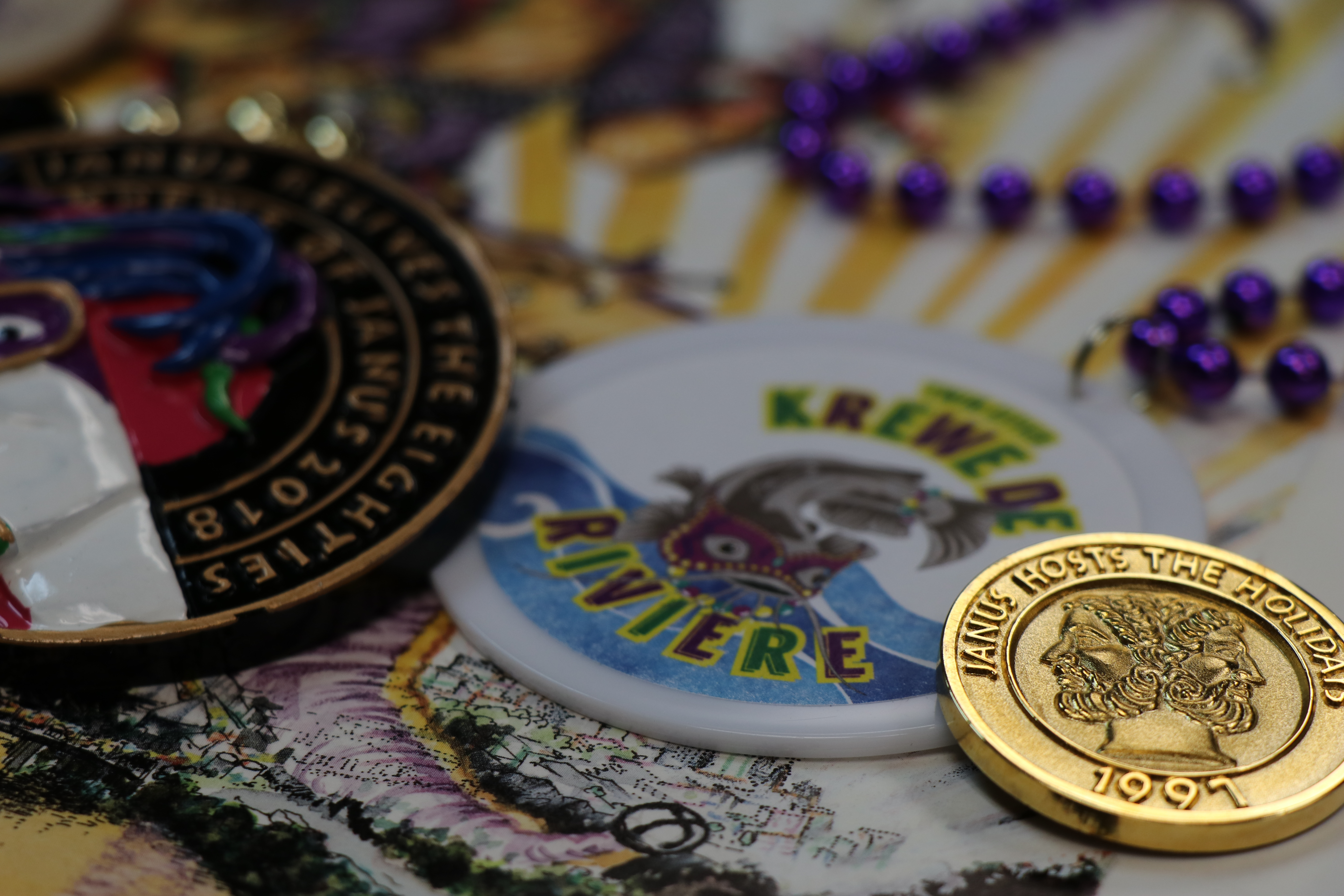 Mardi Gras doubloons and beads are arranged artfully on a table.
