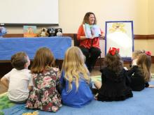 A librarian reads a story to a group of young children who are sitting on the floor around her.